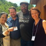 Happy new teachers Bonnie Duran, Tim Geil and Keri Pederson, at Spirit Rock. Embracing them is Andre Alton Hardy, a former Seahawks player who is now an author, grad school student, and partner of Against the Stream co-guiding teacher JoAnna Harper.