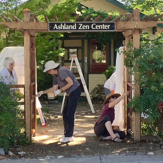 Sangha hands keep the facility in good repair. In 2016, members apply a fresh coat of stain to the entry gate.