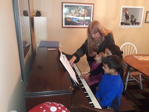 The children learning to play piano.