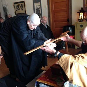Kuya receiving a kyosaku, a stick traditionally used to tap meditators to help them stay alert, during the ordination ceremony.