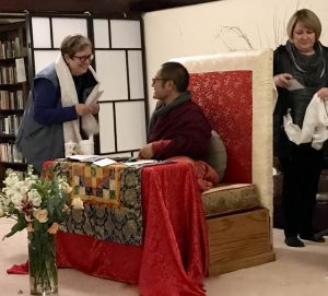 Margaret Cormier making offerings to Adzom Gyalse Rinpoche, with Karen Kolodziejski in the background ready to make an offering to Tashi.
