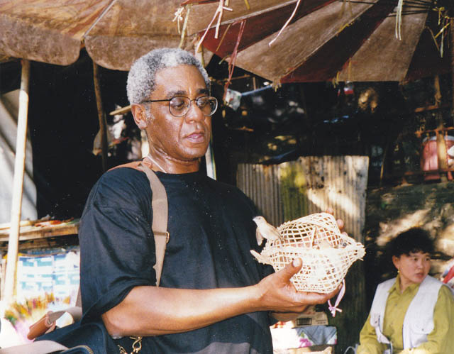 Charles Johnson frees a bird outside a monastery in Chiang Mai, Thailand, during a 1997 trip there.