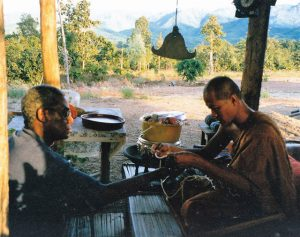 A Thai monks offers Johnson a blessing cord during his 1997 trip.