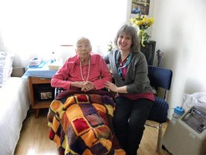 Volunteer Julia Guderian with patient Roberta M, warmed by a blanket that Guderian's son's class knit for this hospice patient.