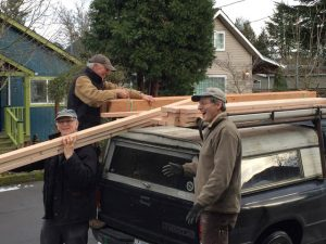 Bill Spangle, Chuck Kangas and Jef Gunn unloading building material.