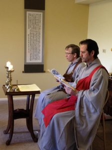 Tim Lerch wears a red kasa over his robe, and Michael Schutzler wears brown, as they lead a precepts ceremony in 2011.
