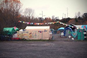 Camp Second Chance's front gate can be seen from Myers Way, and is decorated with a banner made by Nalanda West.