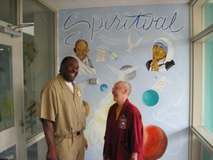 Ji, facilitator-in-training and a mural artist, greets Ven. Gache in the foyer of the education building.