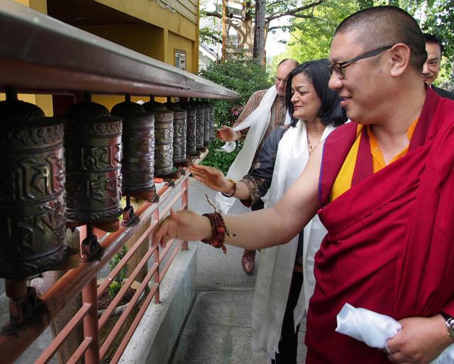 Abbot of Sakya Monastery Khenpo Jampa Tenphel, Congresswoman Jayapal and her husband, spinning prayer wheels outside the monastery.
