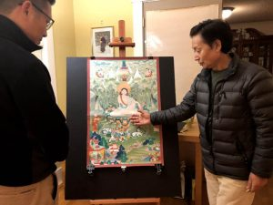 Painter Salga explaining the meaning of some of the detailed art in a Thangka painting to reporter Jamyang Dorjee.