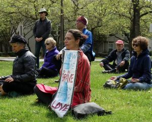 "Anais Tuepker of BPFP and 350PDX sits with her sign for the Llimate Meditation, ""Now is the time to be brave for everything you love."""