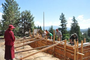 Venerable Thubten Chodron watches a construction crew fill the walls with cement.