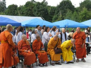 Ajahn Ritthi, standing, greets people at a Mother's Day event