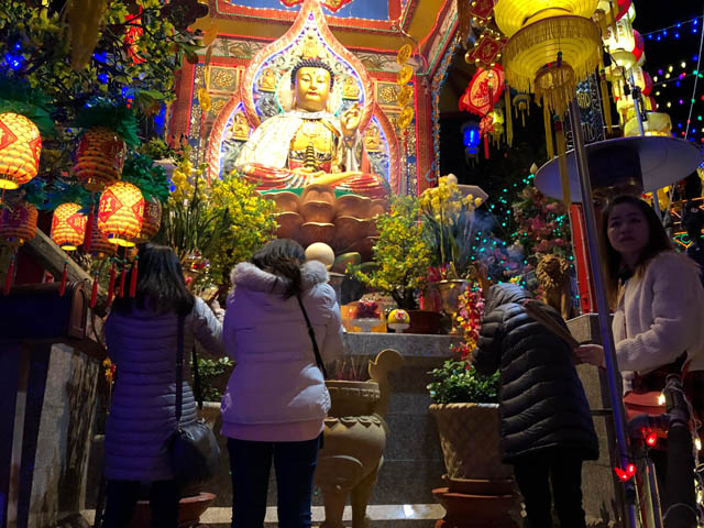 Women with incense bowing to the Buddha, at Dia Tang Temple's Lunar New Year Celebration