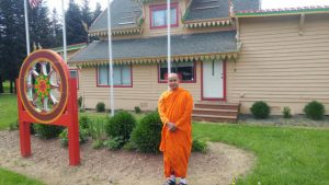 Ven. Aggashri in front of the current building, which features a dharma wheel