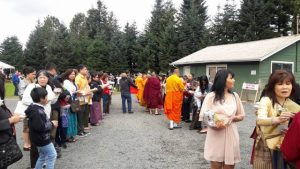 People line up for an alms-giving ceremony, a traditional part of Southeast Asian Buddhist culture