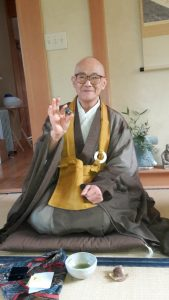 Roshi in his tea house, holding a rock offered by a student