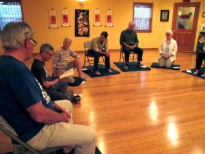 Bart Preces, Mikel Swayze, Trudi Shannon, Karen Kirkwood, Wayne Chabre and Jane Long listen to a reading, before the Sunday evening sitting meditation