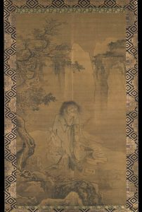 An unkempt Hanshan is shown sitting cross-legged, holding a brush