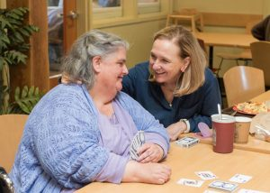 Recovery Café Co-Founder Killian Noe shares a moment with a Member during a card game.