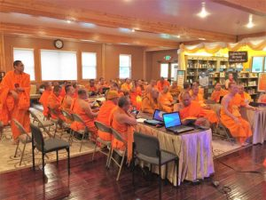 Monks concentrating at a workshop about managing temple finances and computer tools.