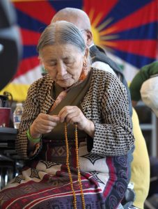 A Tibetan guest at the gathering, chants the beads on her mala