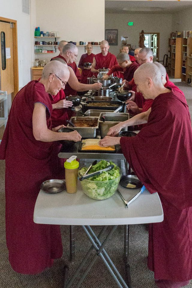 Abbey monastics approach the food serving line in ordination order. Author Ven. Thubten Chodron (right), who is the founder and abbess of Sravasti Abbey, leads the way