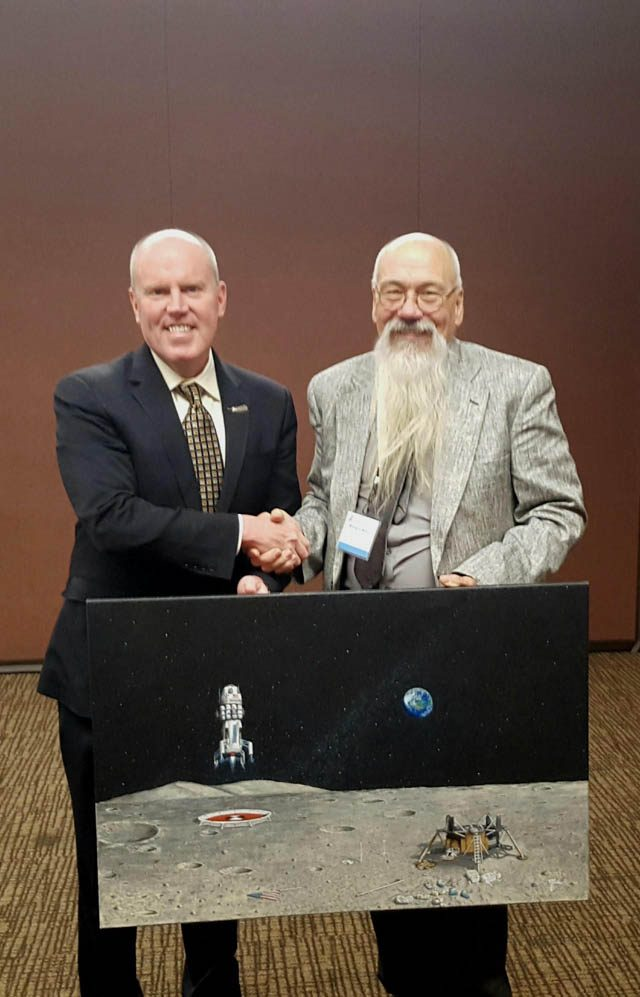 Miles delivering his painting, depicting a future spacecraft tour of the historic Apollo landing site, to Bob Smith, CEO of Blue Origin LLC