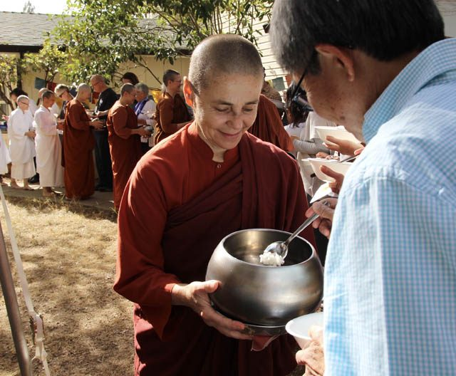 Ayya Santacitta receives ceremonial rice offering on kathina day for midday meal, with the line of all other monastics behind her, walking along the line of lay people offering rice