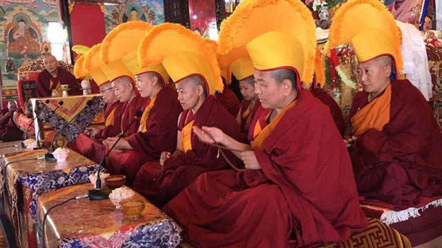 Ten geshemas wearing yellow hats take part in damcha, a formal debate process during which the graduating geshema nuns debate with the other nuns