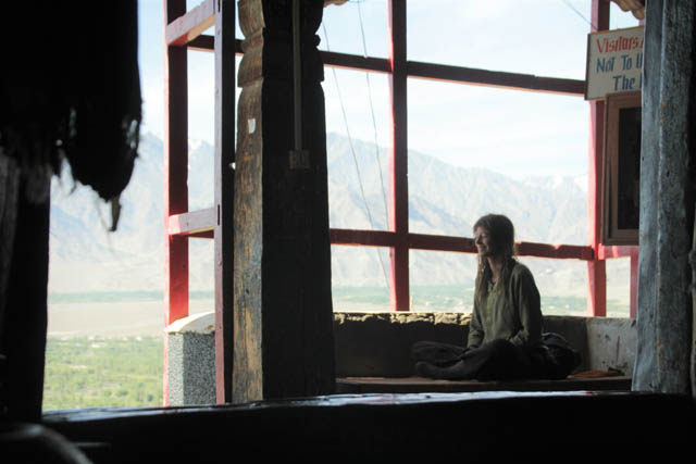 Cate Legate sitting and smiling at Shey Monastery in Ladakh, India, after being fed small bowls filled with Thenthuk, Tibetan noodle soup, by loving monks
