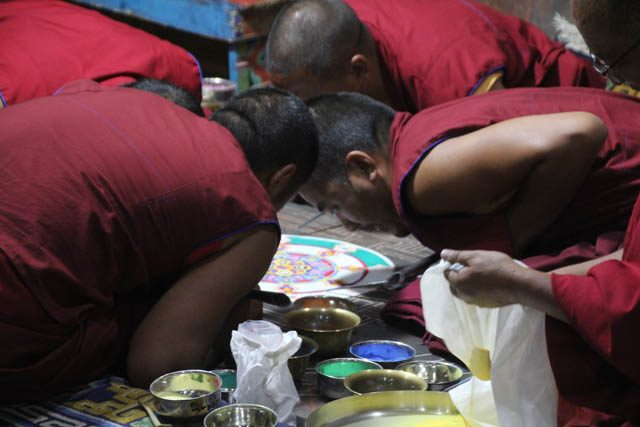 Tibetan Monks near the border of China making a colored sand mandala. After days of focused construction the mandala is destroyed, reflecting the impermanence of life and death