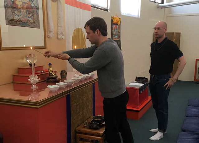 David Cook opens the shrine for the weekly get together of the Young Meditators group. Cory Paulo observes so he can open the following week