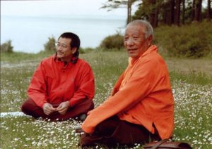 Dzogchen Ponlop Rinpoche, with red jacket and glasses, sits with his teacher Khenpo Tsultrim Gyamtso Rinpoche