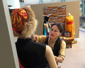 Kelsang Amney fixing up a traditional Tibetan costume on a mannequin