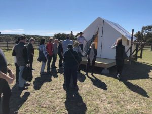 Retreatants tour a prototype of thebluff-top platform tent community currently under construction