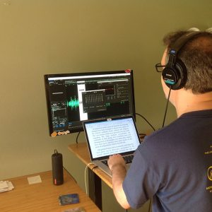 Publisher Steve Hanlon evaluates a volunteer's voice recording, to see if adjustments are needed