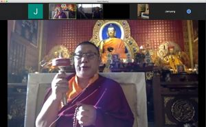 Khenpo Jampa Rinpoche turns a prayer wheel, also on Zoom